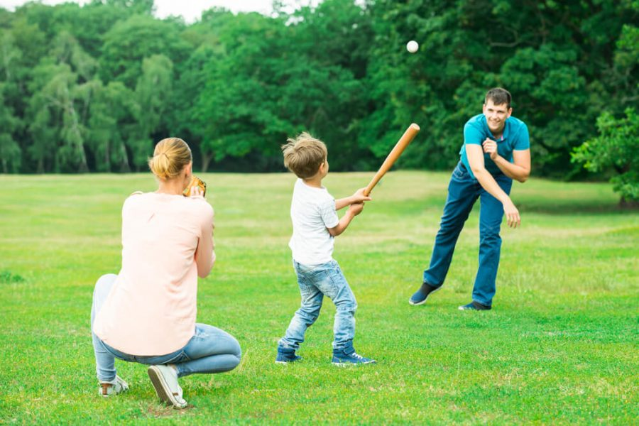 Family Playing Baseball At Park