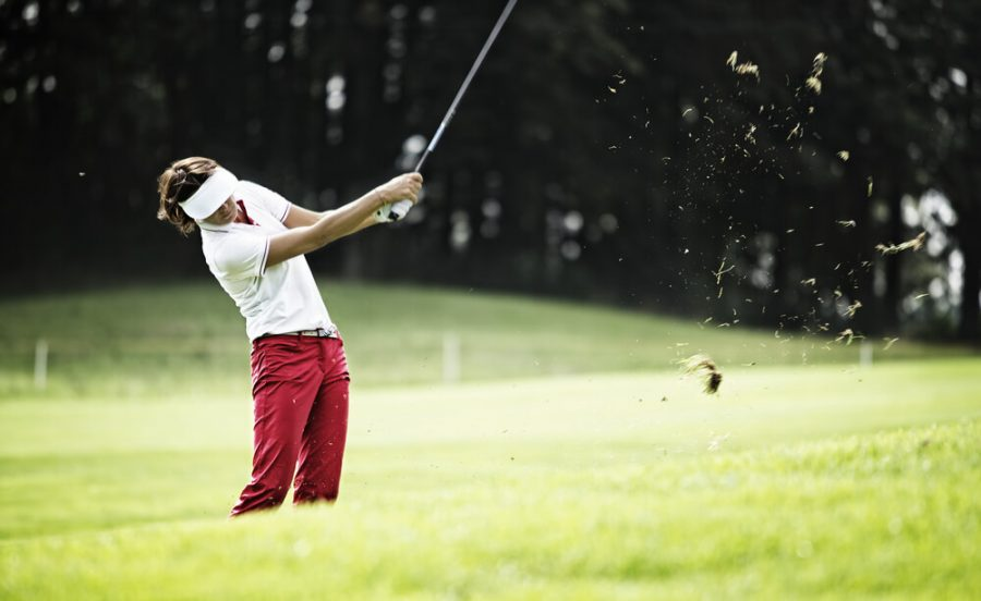 Female golf player pitching