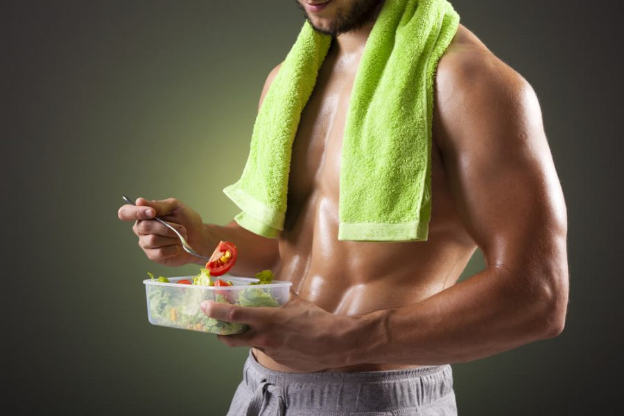 Fitness man holding a bowl of fresh salad