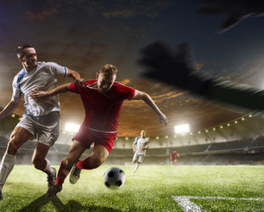Soccer players in action on the sunset