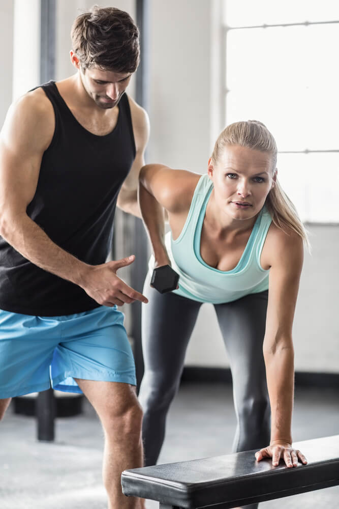 Sporty woman using dumbbells with personal trainor in gym