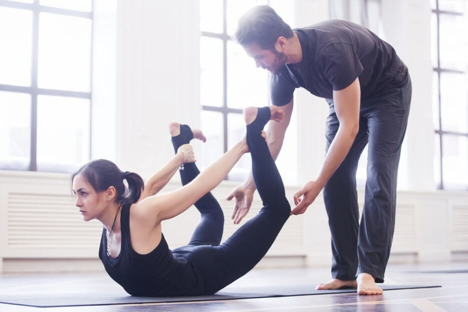 Yoga instructor helps beginner