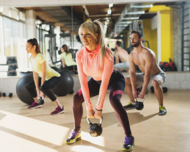 athletes doing exercises with kettlebells