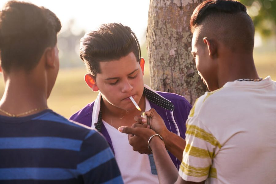 Kids smoking cigarette in park