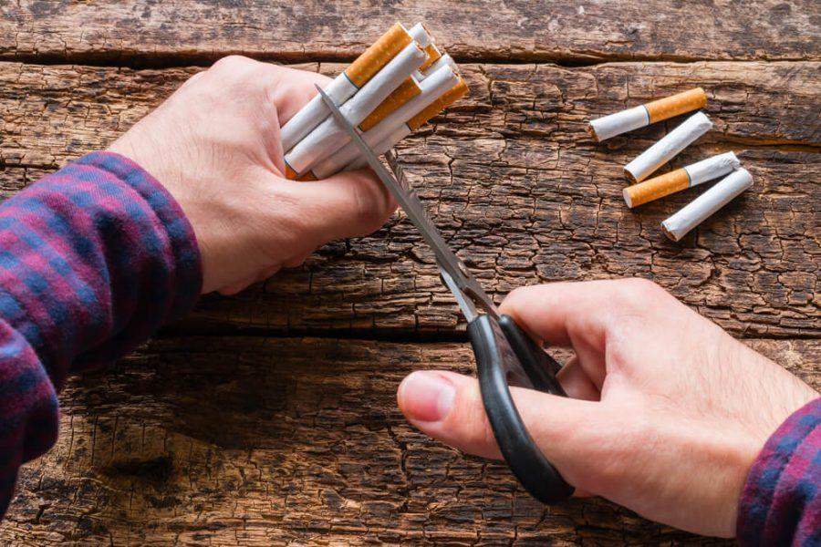 man cuts a cigarette with scisso