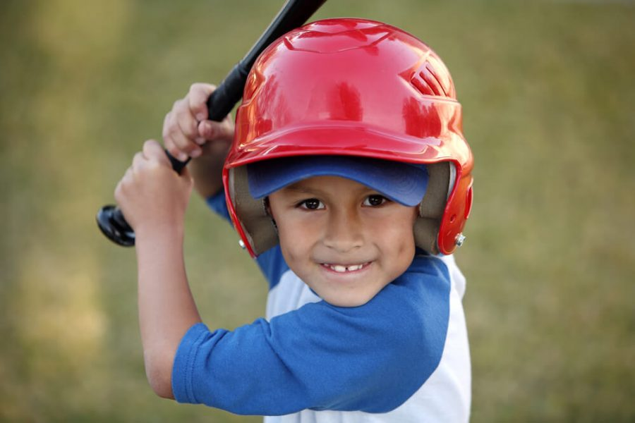 hispanic or latino boy with red baseball helmet