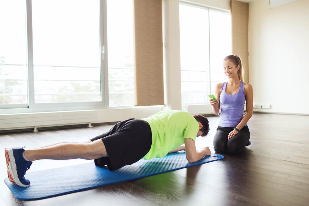 man and woman with smartphone doing plank exercise