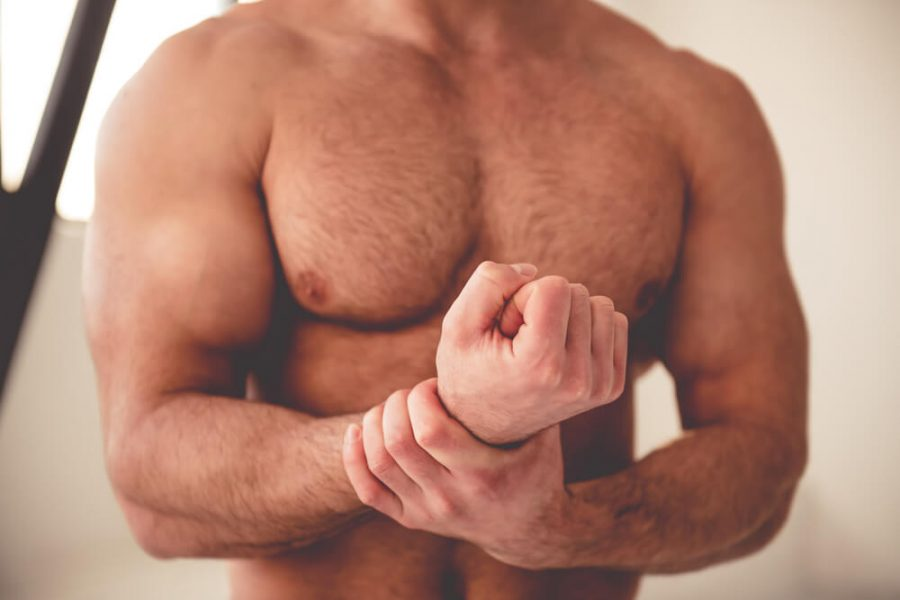muscular man massaging his arms