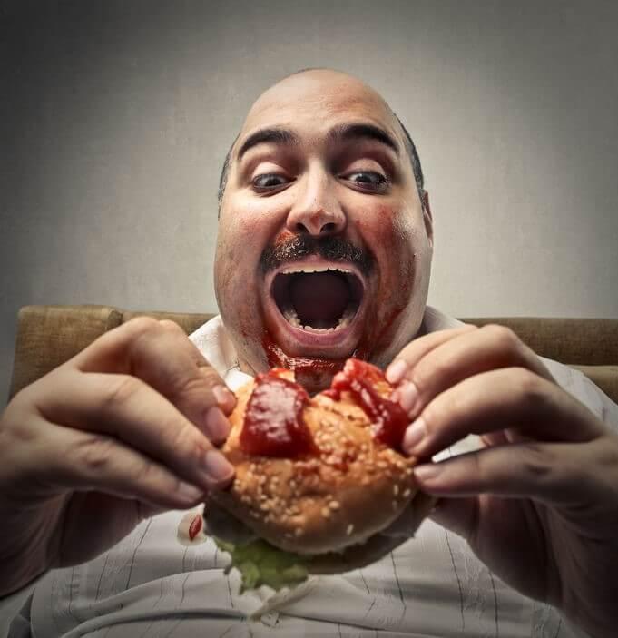50739919 - fat man eating a hamburger