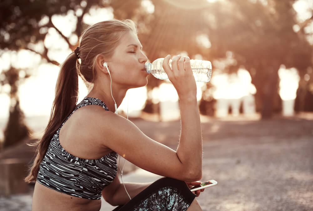 Thirsty female jogger drinking fresh water
