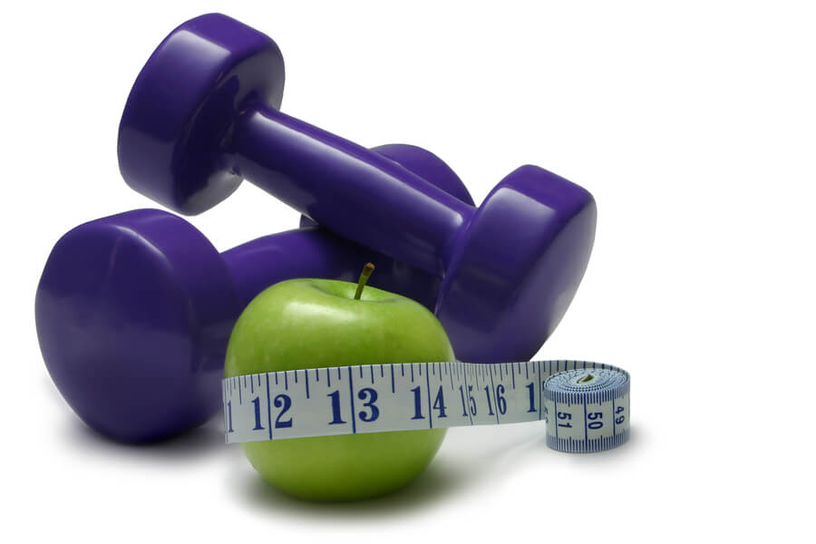 Dumbells green apple and tape measure isolated on white.