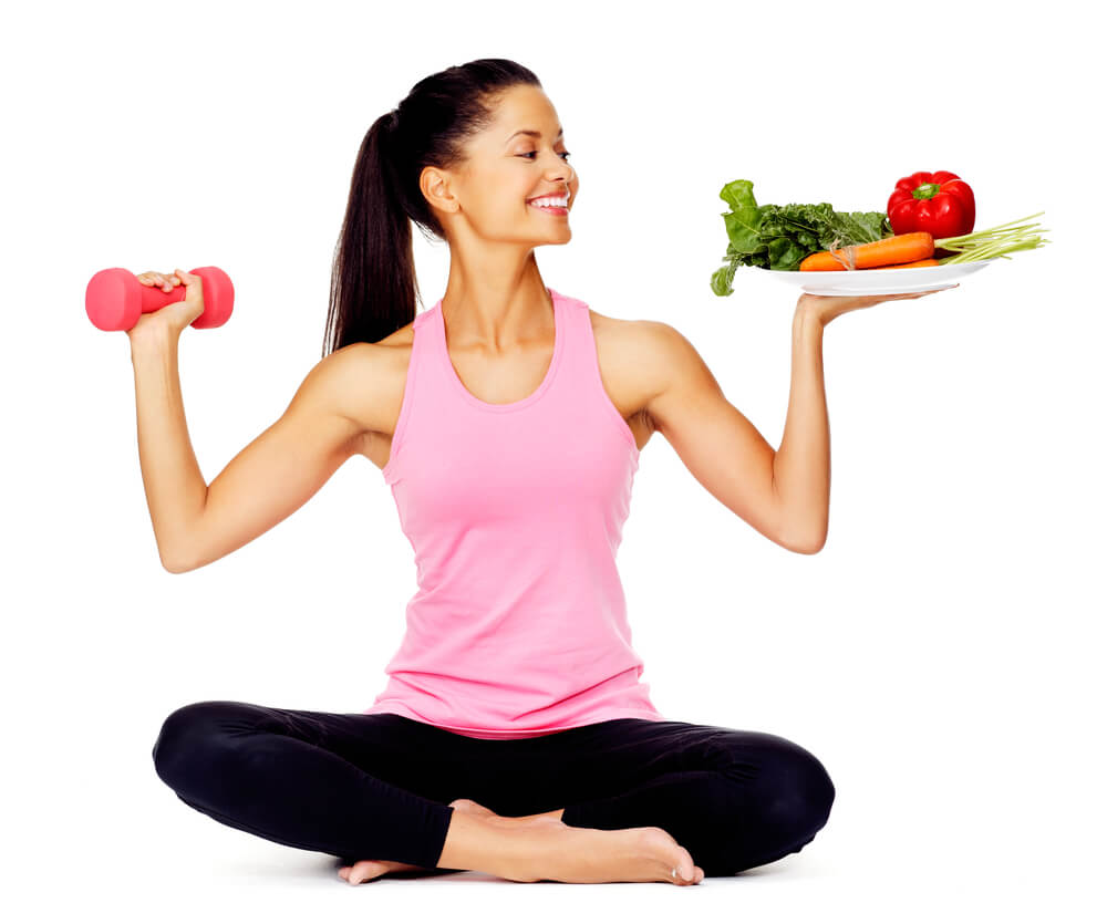 healthy woman with vegetables and dumbbells