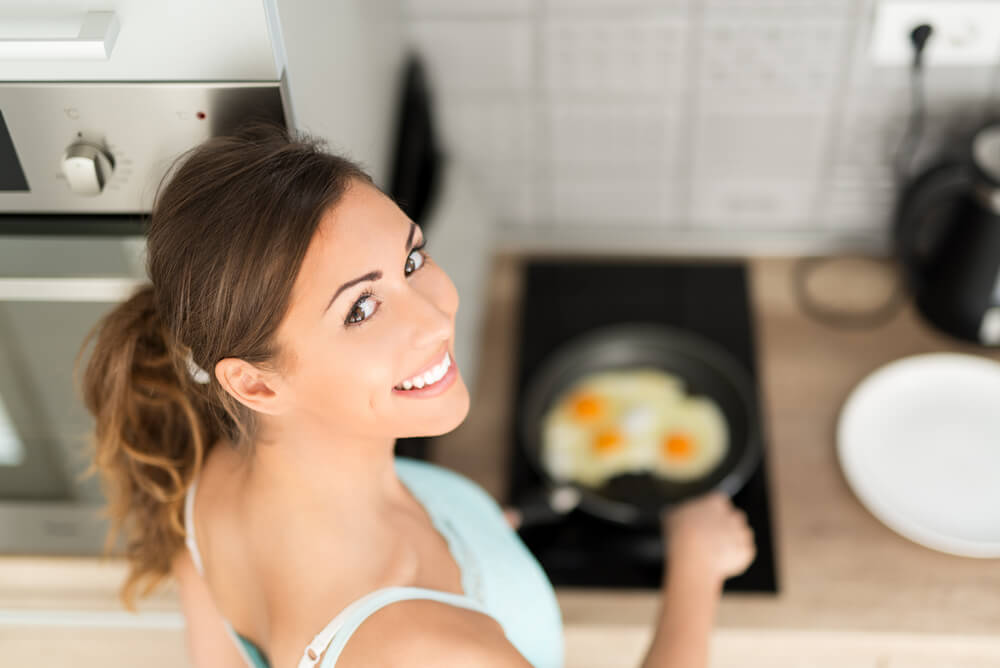 woman cooking eggs for breakfast