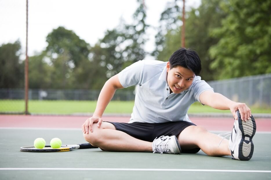 young Asian male tennis player stretching
